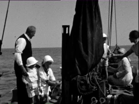 1932 b/w ws pan children in white hats on boat / wyk auf fohr, nordfriesland, germany - tauwerk stock-videos und b-roll-filmmaterial