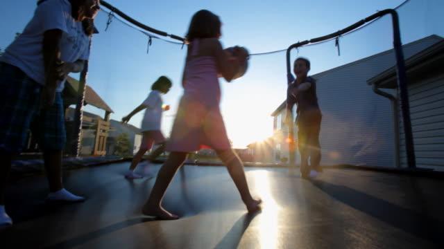 Children jump together on a trampoline at sunset.