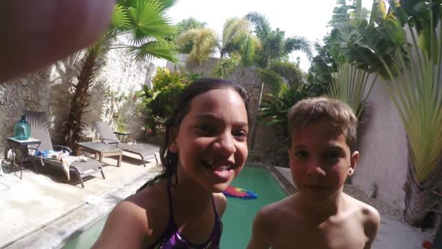 vídeos y material grabado en eventos de stock de children jumping in the pool and taking selfie - mérida méxico