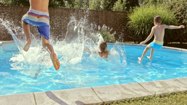 slo mo cs children jumping into the pool in sunshine - fence stock videos & royalty-free footage