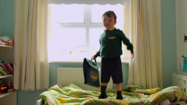 Children jumping on bed with school uniform getting ready for first day back at school