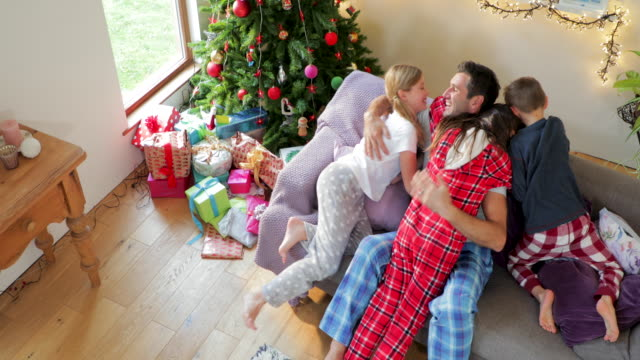 children jumping on father on christmas morning - pigiama video stock e b–roll