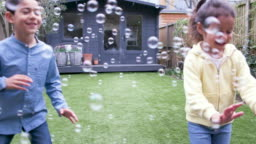 Children laughing and chasing bubbles in the garden