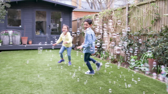 children laughing and chasing bubbles in the garden - domestic garden stock videos & royalty-free footage