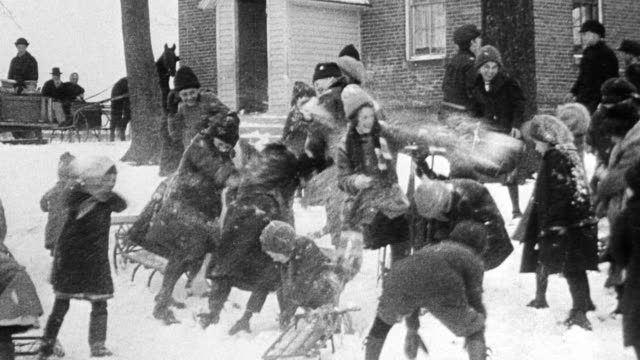 children laughing and engaging in large snowball fight outside school 1916 - 1916 stock videos & royalty-free footage