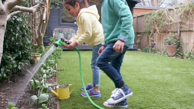 children laughing together while watering the garden - domestic garden stock videos & royalty-free footage