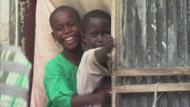 ms children leaning through a doorway, playing and laughing / dakar, senegal - hamlet play stock videos and b-roll footage
