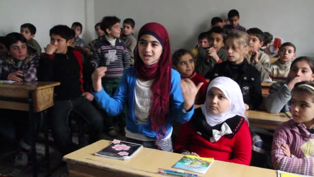 Children learn in a newly opened school in Aleppo Syria