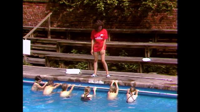 children learn to swim backwards in outdoor pool; 1984 - swimwear stock videos & royalty-free footage