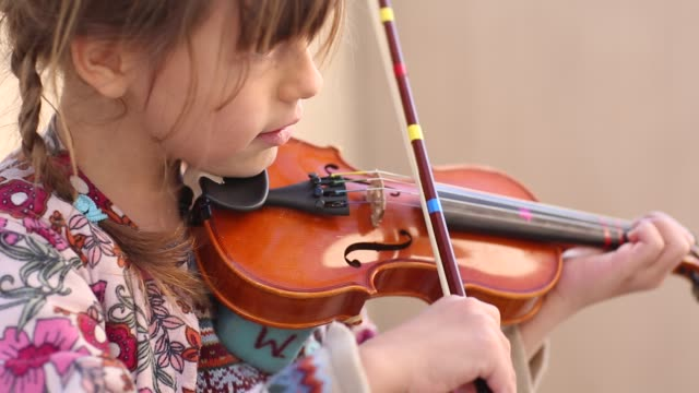 vidéos et rushes de children learning in montessori school environment playing violin - instrument de musique