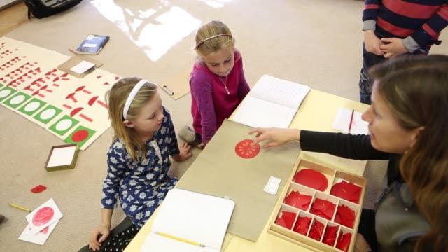 vídeos y material grabado en eventos de stock de children learning in montessori school environment - cinta de cabeza