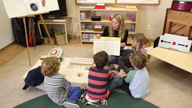 vídeos de stock e filmes b-roll de children learning spanish in montessori school environment - áudio disponível online