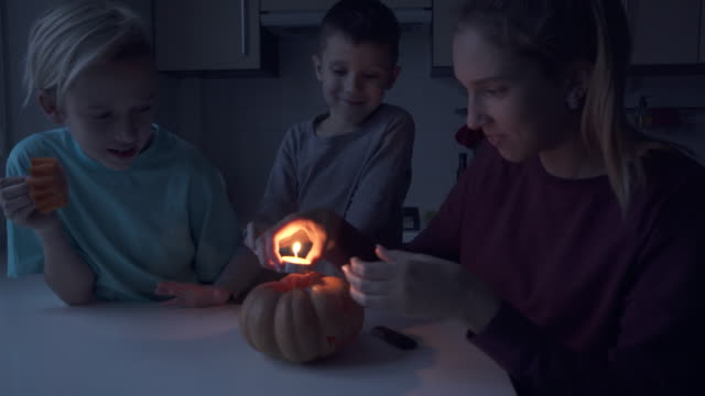 Children lightning a candle and put it in pumpkin