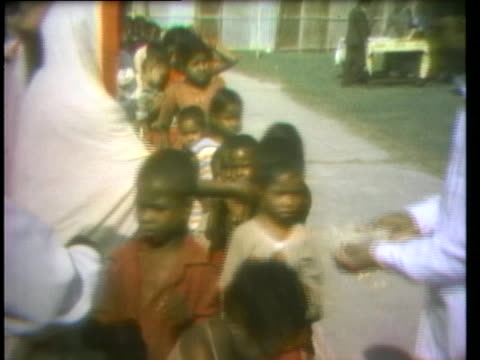 children line up in bangladesh to receive small food packages from relief workers. - 1974 stock videos & royalty-free footage