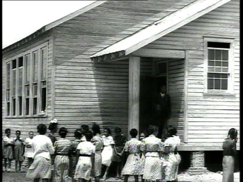 1939 WS children lining up in front of school, teacher stepping onto porch / USA