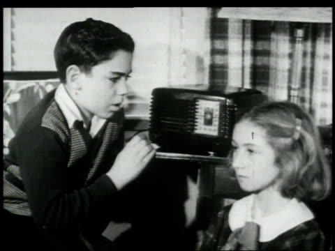 stockvideo's en b-roll-footage met 1948 montage children listening to radio program / united states - 1948