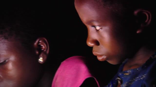 CU R/F Children listening to woman reading by light, Tamale, Ghana