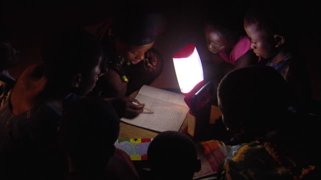 ms ha children listening to woman reading by standing flashlight, tamale, ghana - ghana stock videos & royalty-free footage