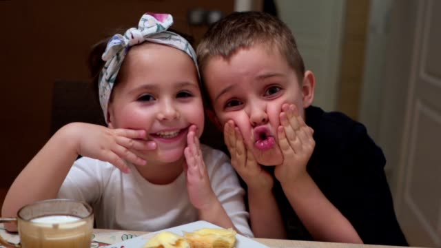 Children making faces while eating a breakfast