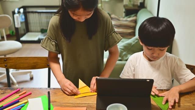 vidéos et rushes de enfants faisant de l'artisanat en papier en étudiant comment faire avec des comprimés. - origami