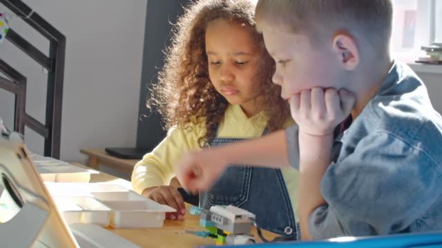 vidéos et rushes de children making plastic model together - modèle réduit