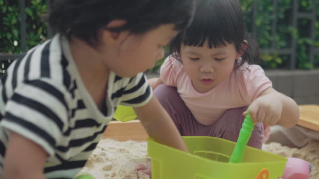 children making sand castle on the dirt ground. - 2 kid in a sandbox stock videos and b-roll footage