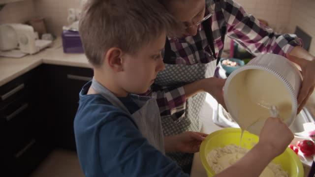 vídeos de stock e filmes b-roll de children making yeast cake - fazer doces