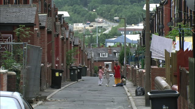 Children meet on a narrow street in Leeds, England.