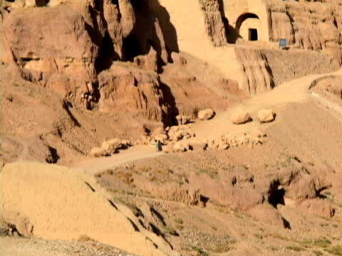 cu zo ws children moving past caves in mountains, bamyan, hazarajat, afghanistan - 遺跡点の映像素材/bロール