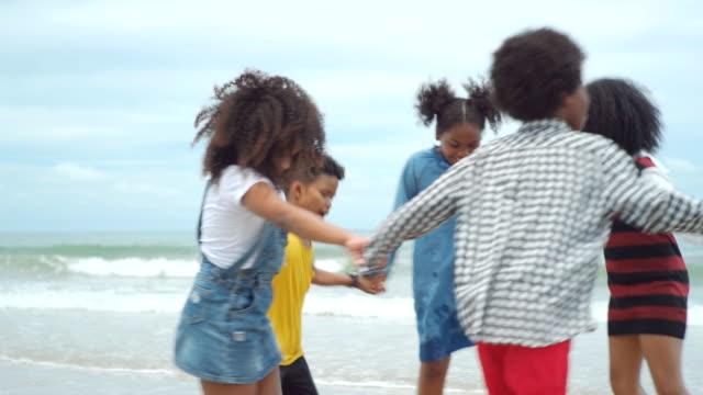 vídeos de stock, filmes e b-roll de crianças amigas multiétnicas brincando na praia no verão - miscigenado