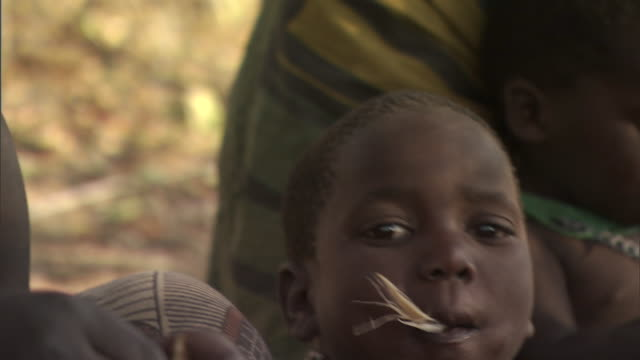 children of the hadza tribe eat banana peels in tanzania. - choker stock videos & royalty-free footage