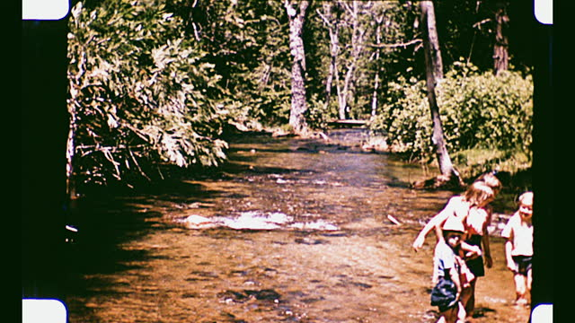 children of various ages crossing a creek while waving and smiling at the camera - yosemite national park stock videos & royalty-free footage