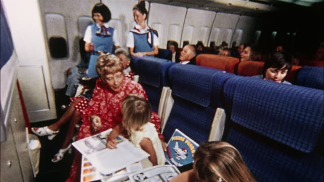 Children on an airplane color and draw using tables at their seats.