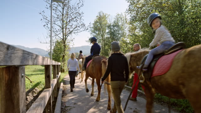children on horses walking across a small bridge in sunshine - horseback riding stock videos & royalty-free footage