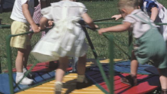 1956 ms tu children on merry go round / usa - 校庭点の映像素材/bロール