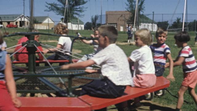 1956 ms children on merry-go-round / usa - playground stock videos & royalty-free footage