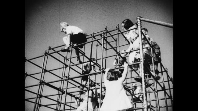 vídeos de stock, filmes e b-roll de children on playground jungle gym on january 01 1939 - jungle gym