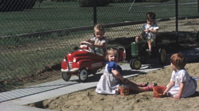1956 montage children on playground, riding toy wagons / usa - 屋外遊具点の映像素材/bロール