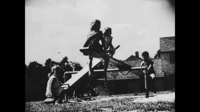 / children on playground see saw. children playing in suburban playground on january 01, 1939 - wippe stock-videos und b-roll-filmmaterial