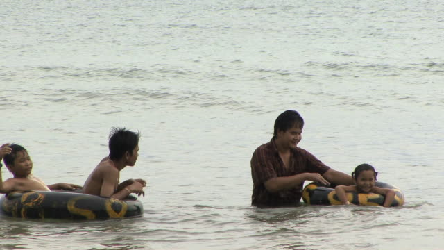 ms children on rubber floats playing in water with fast boats going by, sihanouksville, cambodia - cambodia stock videos & royalty-free footage