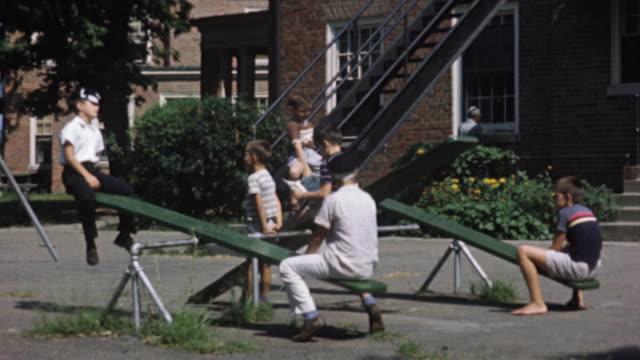 vídeos y material grabado en eventos de stock de 1956 ws children on seesaw on playground / usa - balancín