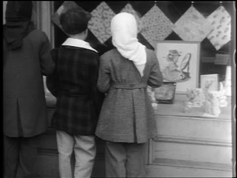 B/W 1944 3 children on sidewalk looking in store window / turn + smile at camera / Lexington, NC