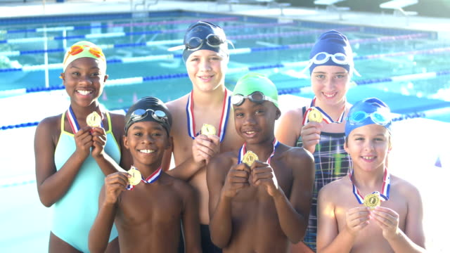 children on swim team proudly holding up medals - podio video stock e b–roll