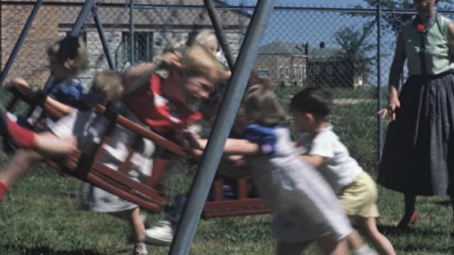 vídeos y material grabado en eventos de stock de 1956 ms children on swings on playground / usa - columpiarse