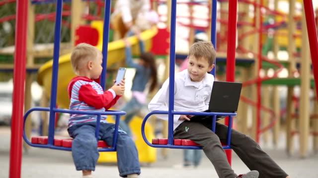 vídeos de stock, filmes e b-roll de filhos no balanço no playground com dispositivos - equipamento