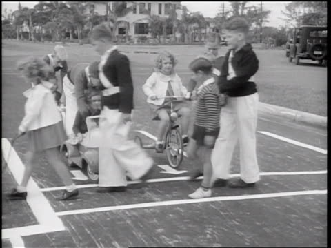 b/w 1936 children on toy cars + tricycle at crosswalk as crossing guards guide pedestrians across - tricycle stock videos & royalty-free footage