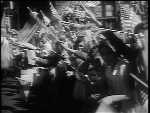 b/w 1932 children onlookers waving american flags at parade with civil war veterans - 1932年点の映像素材/bロール