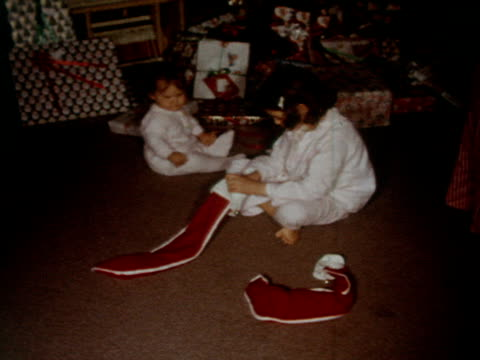 children open gifts and stockings on christmas morning. - 1962 stock-videos und b-roll-filmmaterial