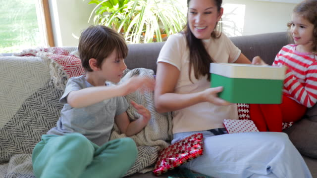 Children Opening Christmas Presents on Sofa