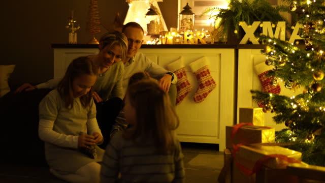 children opening christmas presents - familie mit drei kindern stock-videos und b-roll-filmmaterial